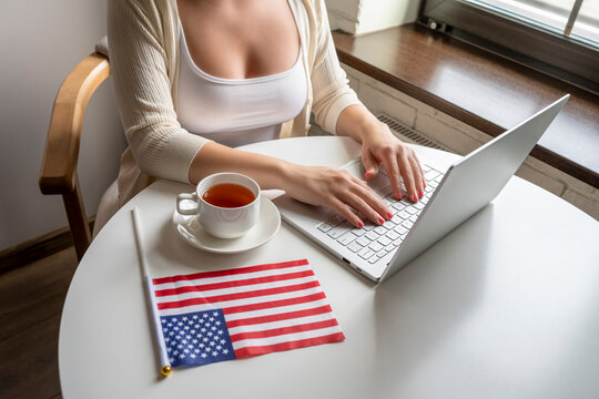 Lonely woman freelancer with flag of America enjoying having breakfast with cup of coffee working on laptop sitting near window in cafe at morning.