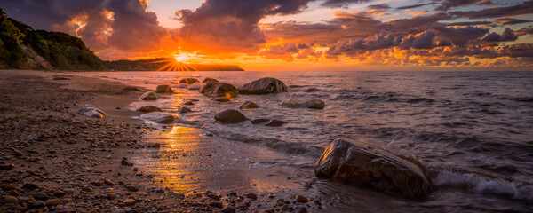 Colorful sunset over the sea and rocky shore