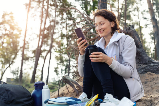 Young adult caucasian beautiful attractive female person enjoy having fun use phone and drink warm drink at picnic hiking trip pine forest wood autumn day. Family nature outdoor recreation lifestyle