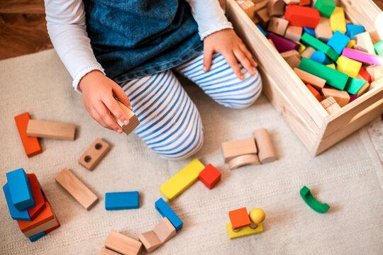 Little girl playing with wooden bricks at home.