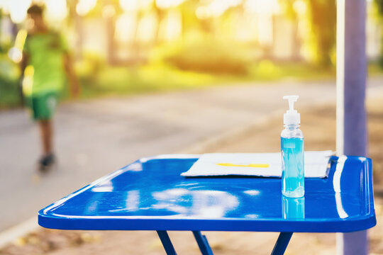Blue alcohol gel bottle and a register book on the table for athletes to prevent Corona Virus (COVID -19) infection and spread before exercising in public park. New normal lifestyle. Selective focus