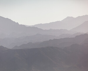 Silhouetted landscape of mountain ridges at sunset or in the fog.