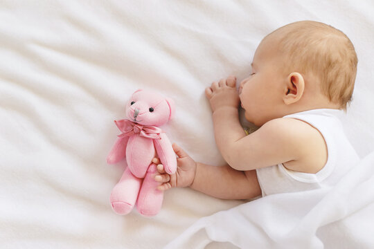 Baby sleeps with a teddy bear on a white background. Selective focus.
