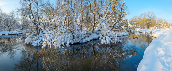 Frosty winter scene with flowing forest river on a sunny morning.