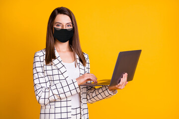 Photo portrait of pretty woman keeping laptop wearing black face mask smiling isolated on bright...