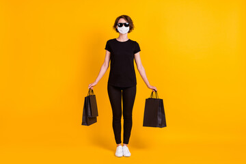 Full length body size view of fashionable cheerful girl carrying bags use safety mask isolated...
