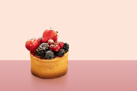 mini cake decorated with variety of berries on colorful background