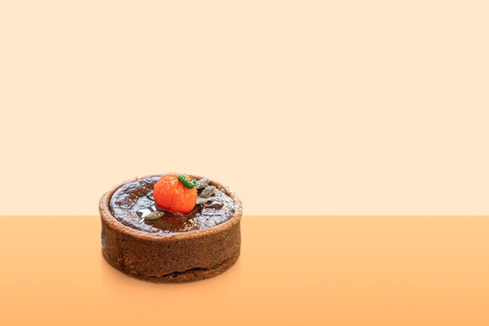 mini chocolate cake decorated with sugar pumpkin on colorful background