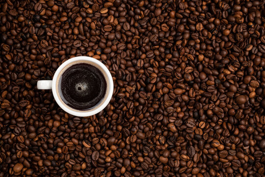 cup full of black coffee over a background of coffee beans