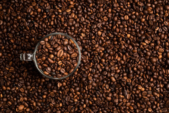 glass cup full of coffee beans over a background of coffee beans