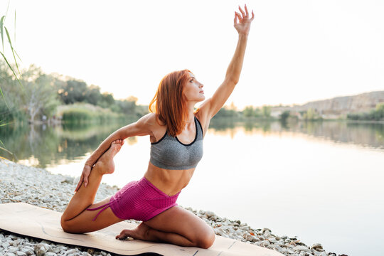 Young woman practicing yoga at the edge of a lake