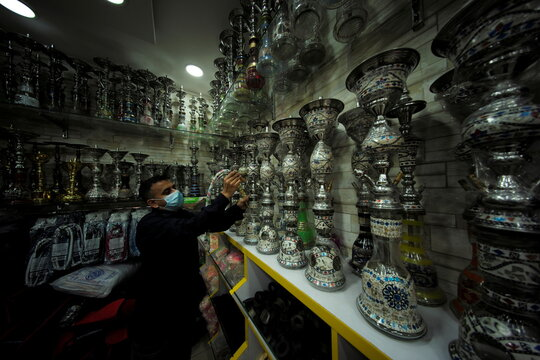 A salesman fixes a smoking pipe to a hubbly bubbly (shisha) at his tobacco and shisha shop, following the outbreak of the coronavirus disease (COVID-19), in Manama