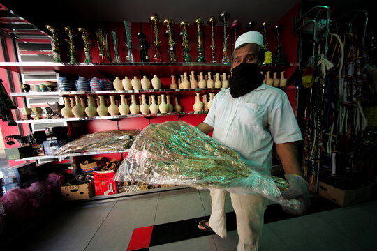 A salesman shows raw tobacco leaves at his tobacco and shisha shop, following the outbreak of the coronavirus disease (COVID-19), in Manama