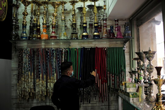 A salesman arranges smoking pipes used in hubbly bubbly (shisha) at his tobacco and shisha shop, following the outbreak of the coronavirus disease (COVID-19), in Manama