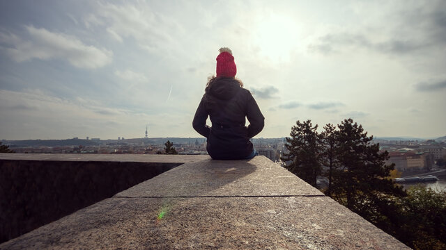 Woman in winter jacket sitting on a wall and looking at the panorama of Prague