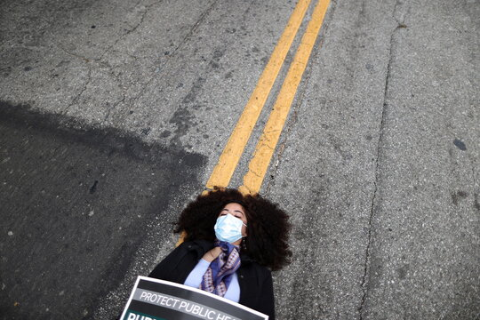 A woman lies in the road outside the LA Board of Supervisors during a die-in protest and memorial service honoring the over 6,800 people from LA who died from the coronavirus disease (COVID-19), in Los Angeles