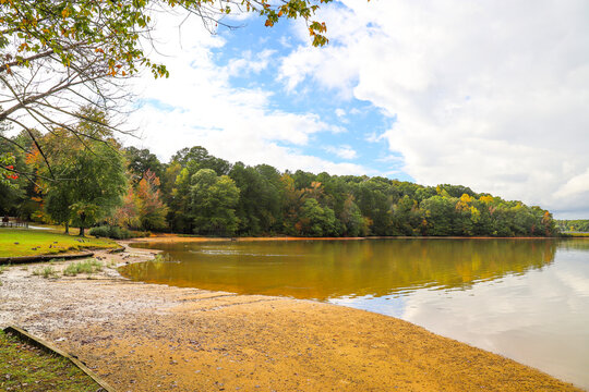 a breathing taking shot of the vast still lake water with blue sky, clouds and lush green and autumn colored trees reflecting off the lake at Sweetwater Creek State Park in Lithia Springs Georgia