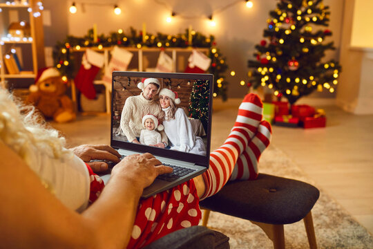 Relaxed Santa with laptop having online video call with happy family on Christmas Day