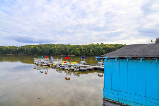 colorful boats at the dock in the middle of the lake with lush green and autumn colored trees and a blue boat house at Sweetwater Creek State Park in Lithia Springs Georgia