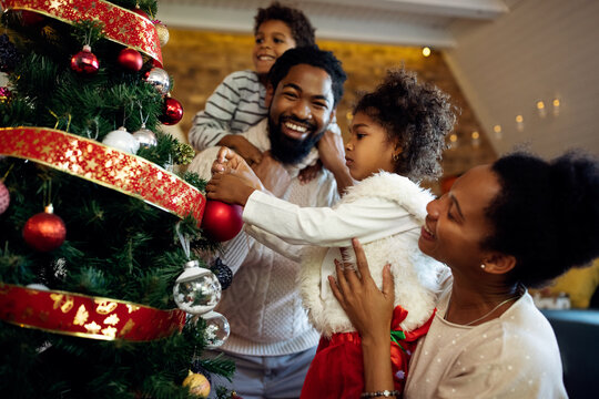 Happy black family having fun while decorating Christmas tree at home.
