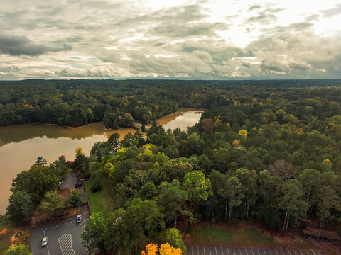 a breathing aerial taking shot of vast miles of lush green and autumn colored trees with majestic blue sky and powerful cloud covers at Sweetwater Creek State Park in Lithia Springs Georgia