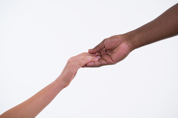 Mixed race couple holding hands. One caucasian and one african hand on white background. Concept of caring and tenderness. Male and female hands touch each other. Wall mural