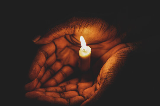 burning candle in hand