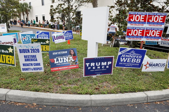 Campaign signs are posted near the Supervisor of Elections Office polling station while people line up for early voting in Pinellas County ahead of the election in Largo