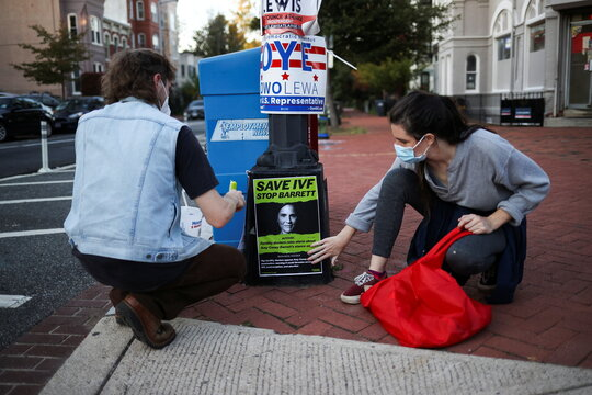 People attach an Anti-Judge Amy Coney Barrett poster to a lampost, on Capitol Hill, in Washington D.C.