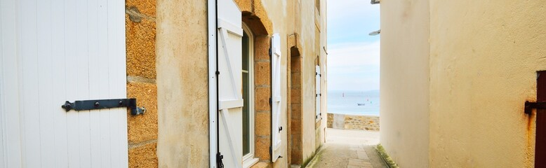 Narrow street passage at Ile de Sein, France. Panoramic view. Old traditional houses close-up. Travel destinations, vacations, landmarks, sightseeing, architecture Fotomurales