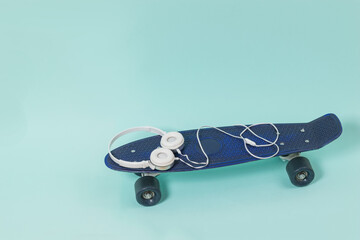 White headphones lying on a blue skateboard on a light background. Place for text.
