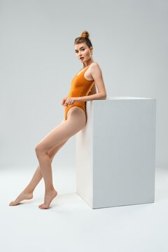 Fit woman in sportive bodysuit standing in light studio