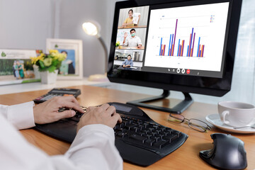 Fototapeta Hand of businessman and businesswoman analysis financial chart with videoconference online meeting. Hand of businesswomen using laptop meeting with diverse colleagues. Covid-19 working from home.