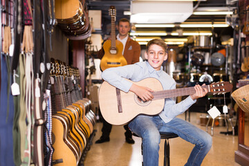 .Smiling boy adjusts guitar in music store