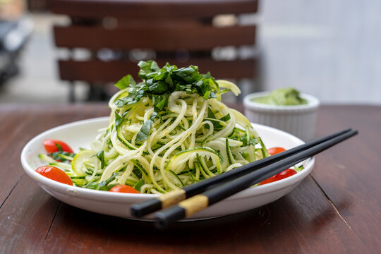 Noodles of spiralized zucchini, cucumber, cherry tomato, garlic in a creamy pesto from avocado. Raw food for vegetarian