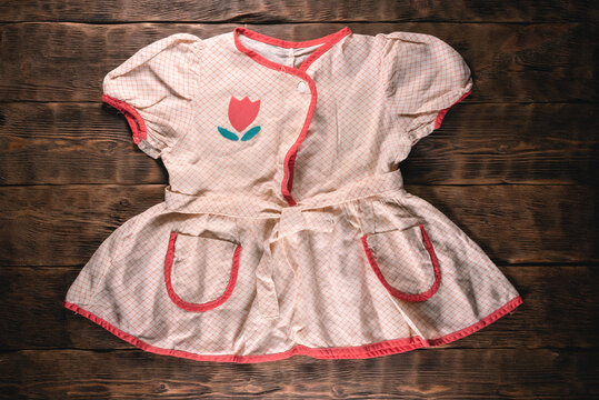 Old retro children girl dress on the brown wooden table flat lay background.