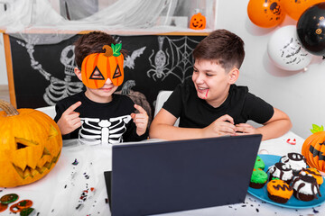 Photo sur Plexiglas Dinosaurs Happy young boys, brothers talking with grandparents via video call using laptop on halloween day , excited kid showing his new mask for halloween on camera