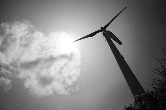 Wind turbine against sky in black and white. Wind power plant clean enegy