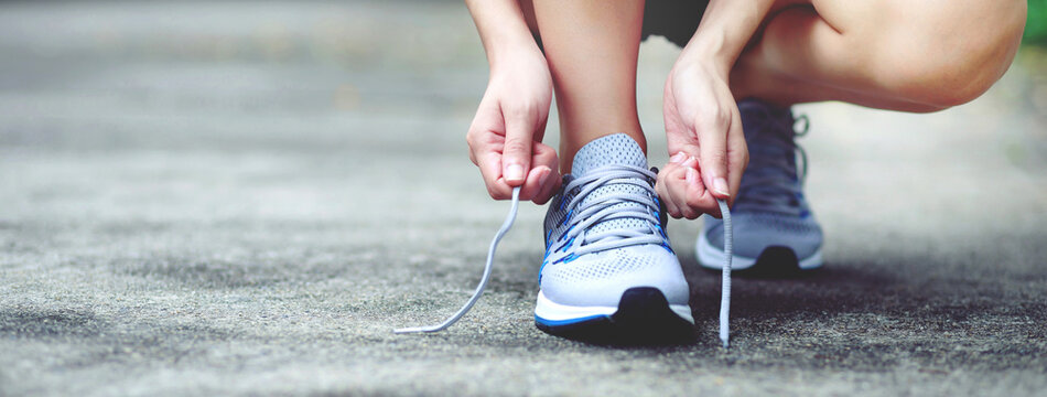 Running shoes. close up female athlete tying laces for jogging on road. Runner ties getting ready for training. Sport lifestyle. copy space banner.
