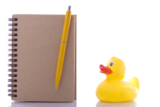 spiral craft notebook, pen for business concept with duck on white background