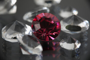 On black background there are transparent gemstones transparent and burgundy. Selling gemstones concept