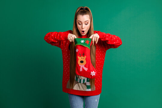Photo of attractive shocked lady hold newyear stocking x-mas present family tradition look inside open mouth long-waited gift wear red ugly ornament pullover isolated green color background