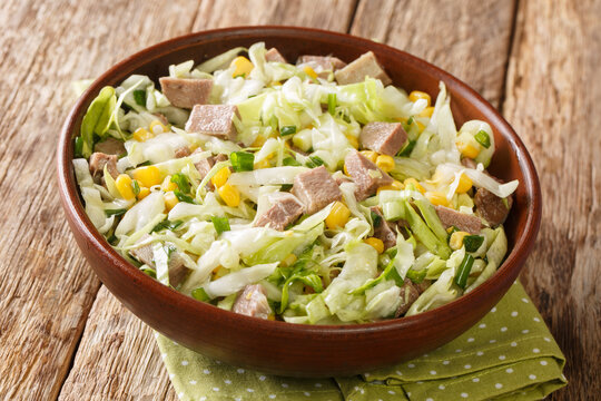Homemade delicious salad with beef tongue, cabbage and corn close-up in a bowl on the table. horizontal