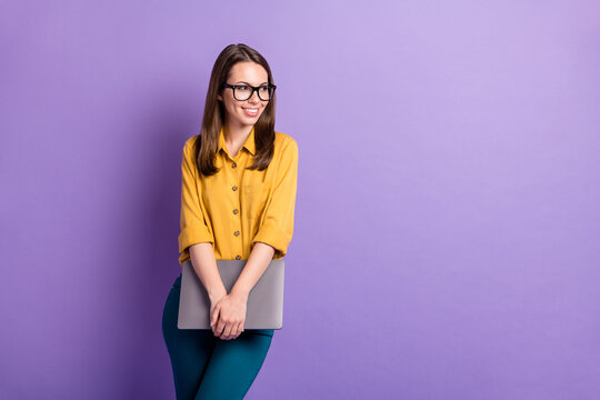 Photo of charming girl hold pc look side empty space wear specs yellow shirt blue pants isolated purple color background