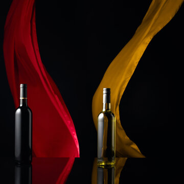 Red and white wine on a black reflective background.