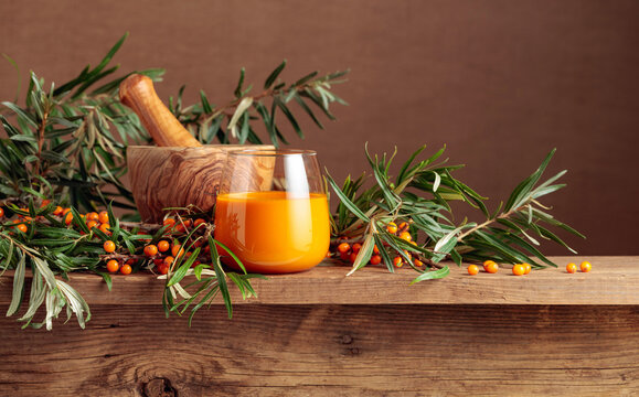 A glass of sea buckthorn juice with fresh berries on an old wooden table.