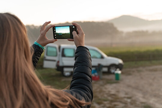 Young pretty woman taking a picture with her phone traveling by camper van though the countryside. Self built off-grid motorhome. Van life wild sunset.