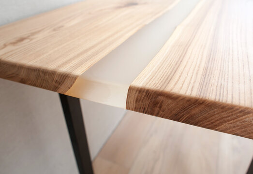 Wooden stylish table made of solid wood with epoxy resin on the background of the floor and wall. Close-up