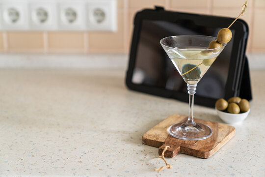 COvid-19 concept - quarantini drink martini via online communication with tablet, kitchen background