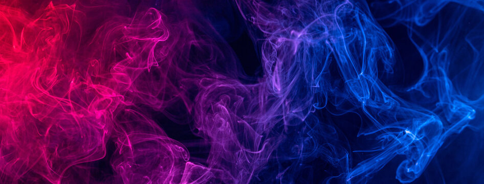 Conceptual image of colorful red and blue color smoke on dark black background.